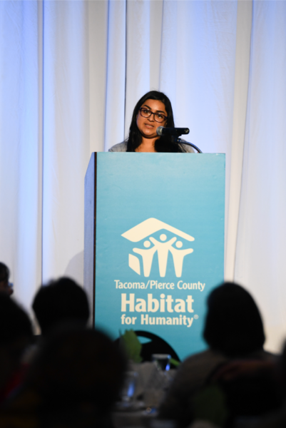 photo of Habitat homeowner Nancy, standing at a podium and addressing a crowd at the 2020 lunncheon